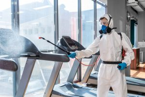 Worker disinfecting gym equipment using Electrostatic Sprayer for COVID-19