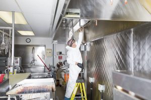 Worker cleaning and degreasing a restaurant kitchen