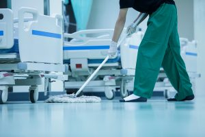 Cleaning professional mopping floor in a hospital