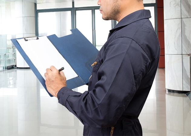 Worker providing quality control inspection on clipboard