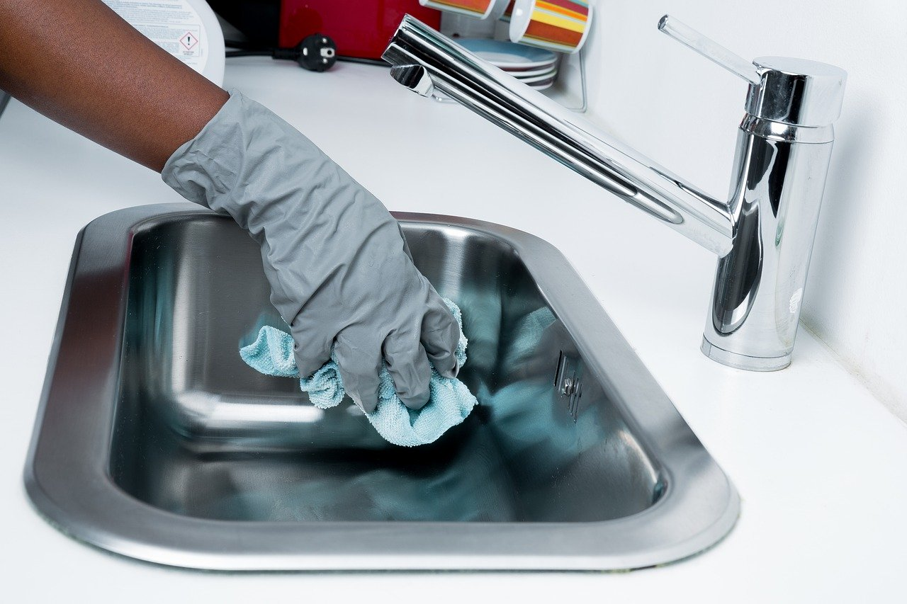 Worker cleaning a sink in a commercial building with gloves